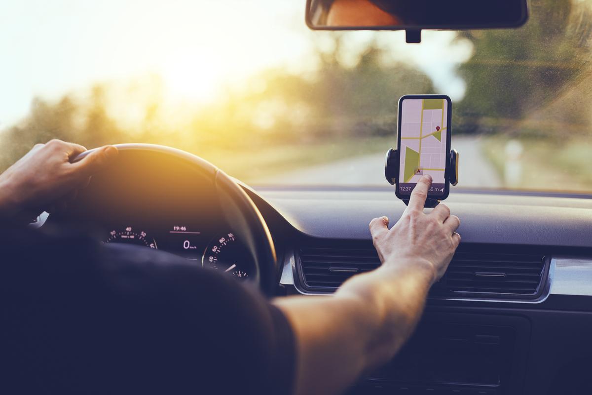 Un guidatore al volante imposta il navigatore offline sulla propria vettura