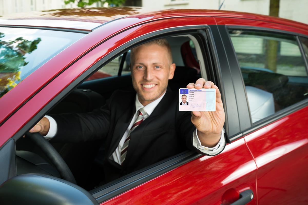 Un uomo mostra la sua patente di guida