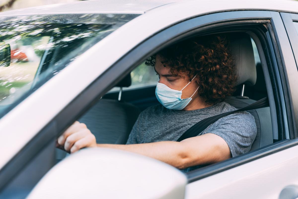 Un ragazzo indossa la mascherina in auto