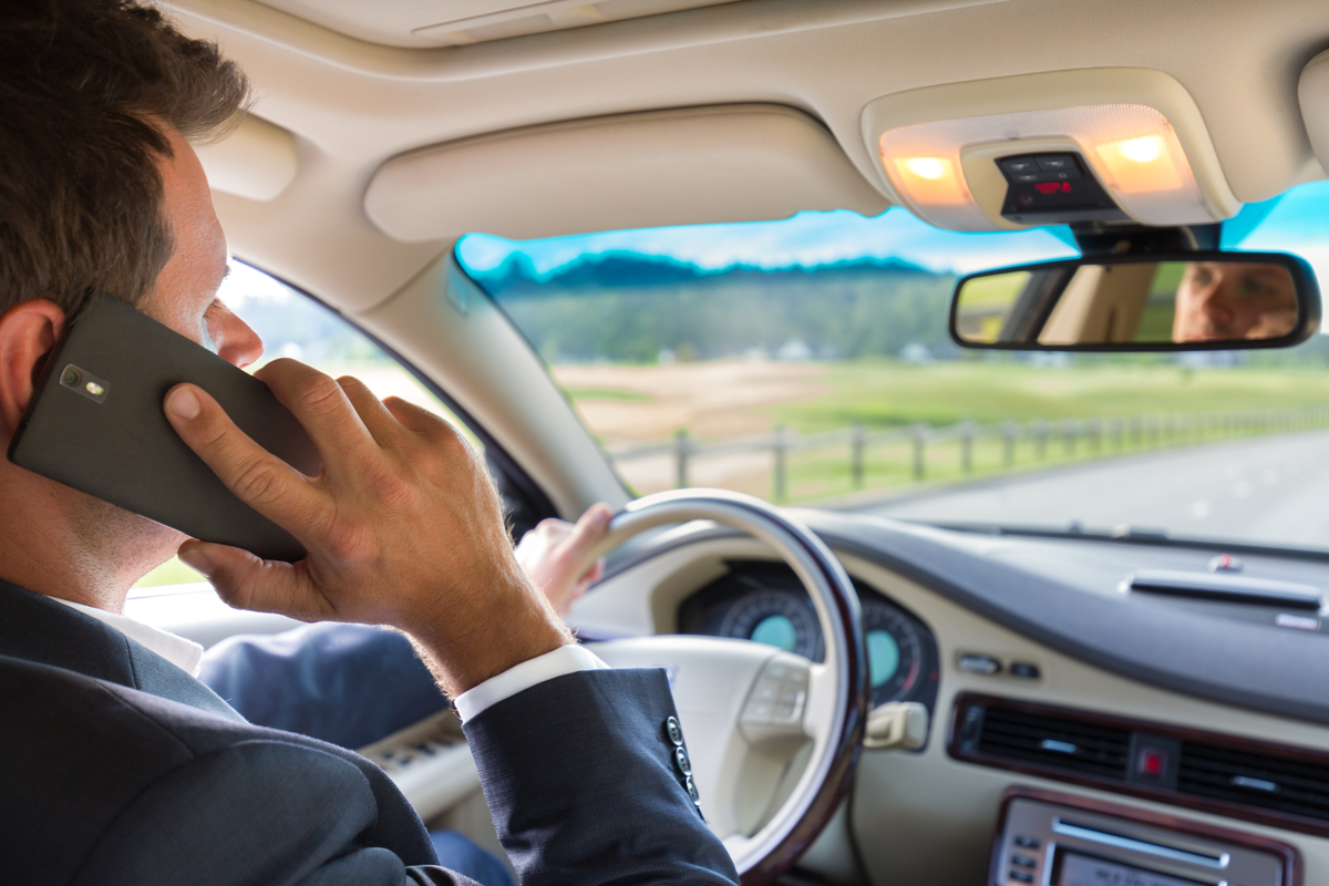 Un uomo al telefono mentre guida