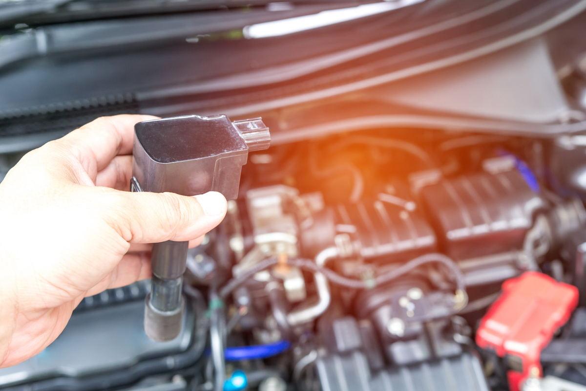Uomo monitora e sostituisce bobina di accensione dell'auto