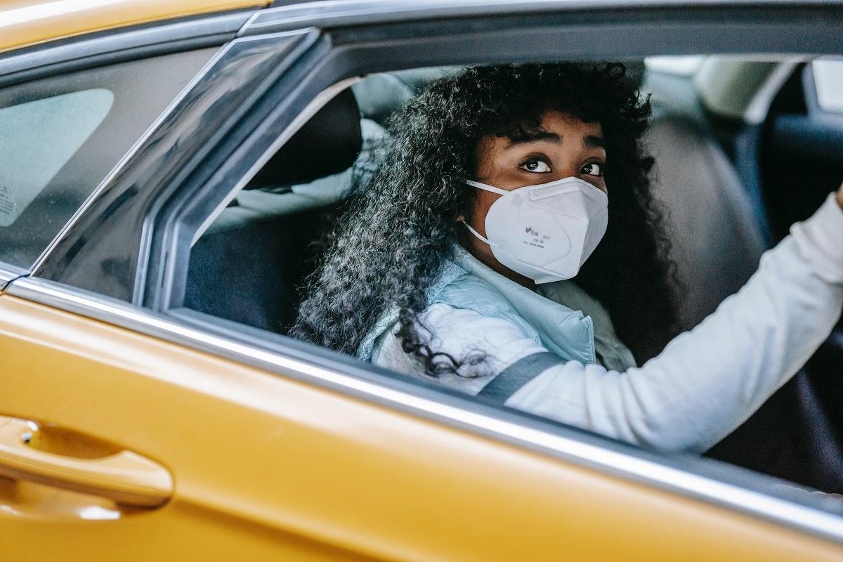 ragazza con mascherina in automobile